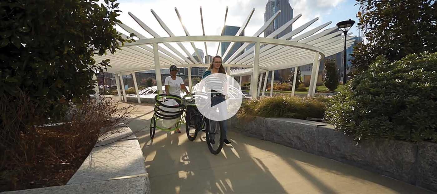 Video thumbnail of a person walking a bike through a garden with a trashcan.