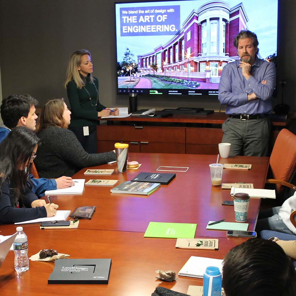 "A board room meeting with a slide on a screen that reads ""We blend the art of design with the art of engineering."""