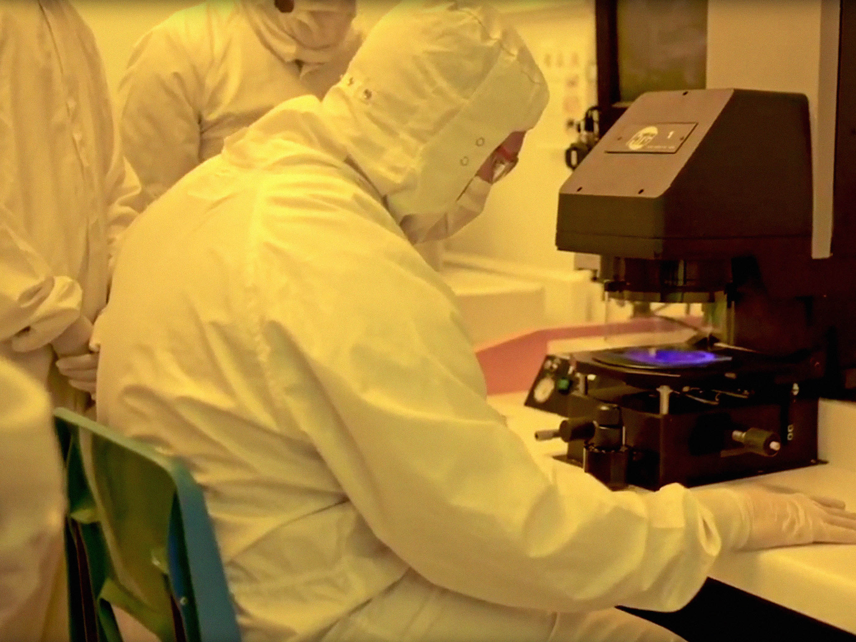 Scientists in lab with solar cells and microscope